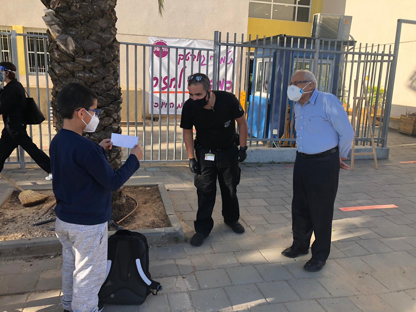 ראש העיר מוטי ששון בוחן הצהרת בריאות של תלמיד בעת פתיחה מחודשת של בית הספר גולדטק בחולון בצל מגבלות הקורונה. צילום-עיריית ח (1)