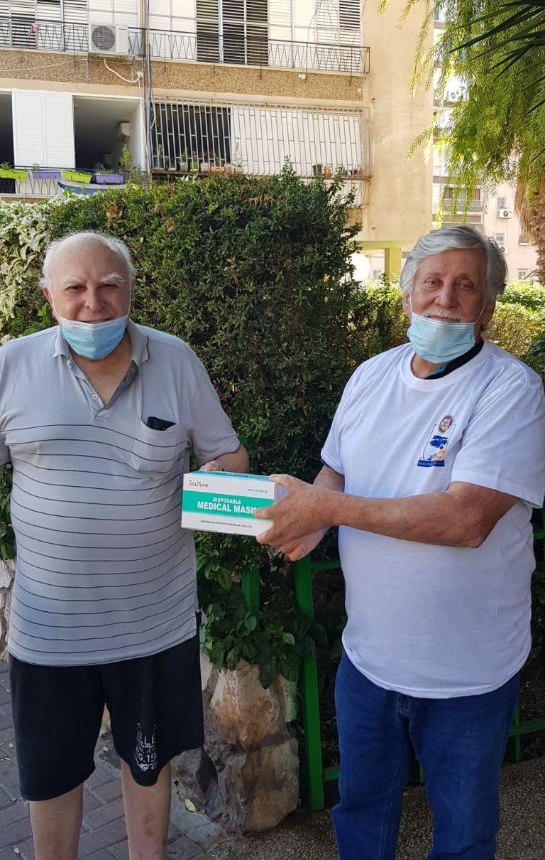 מימין-מתנדב רוטרי ויקיר העיר נתן שרפמן מעניק חבילת מסכות ליקיר העיר ניסן שאלתיאל. צילום-באדיבות רוטרי חולון