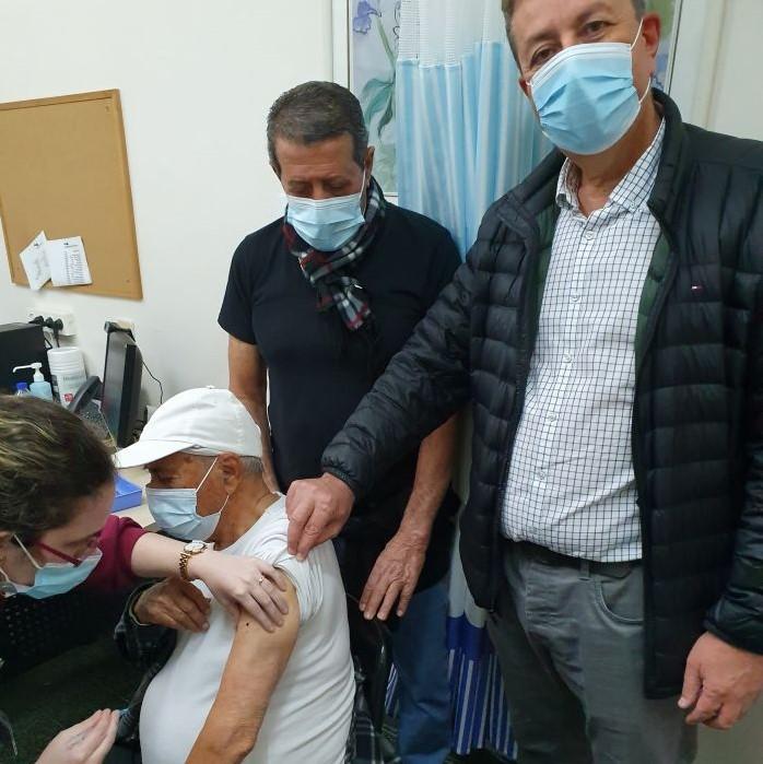 ששון בן יעקב מקבל חיסון כשהוא מלווה בראש העיר ישראל גל (מימין) ובבנו אברהם (במרכז). צילום: עיריית קריית אונו