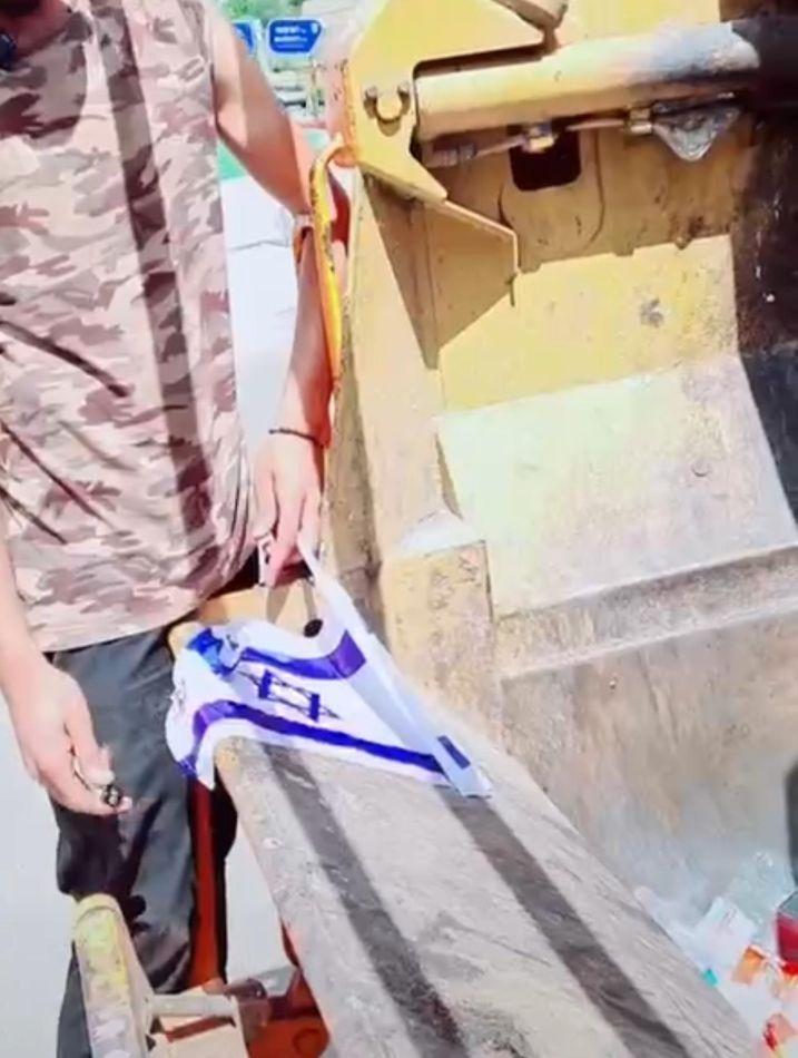 העובד מצית את דגל ישראל- צילום מסך מתוך הסרטון